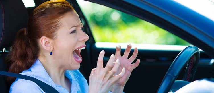 woman inside her car, frustrated and angrily screaming